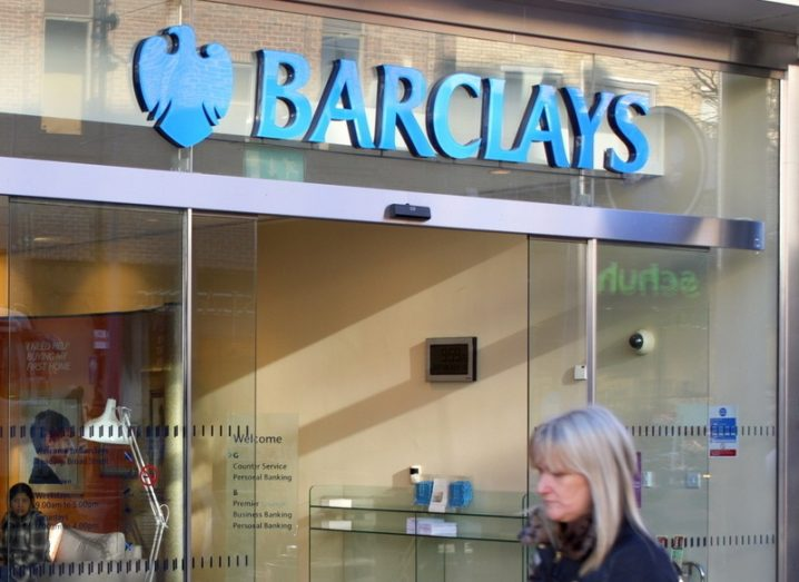 Exterior of a Barclays bank branch in Reading, Engliand with a blonde woman passing in front of it.