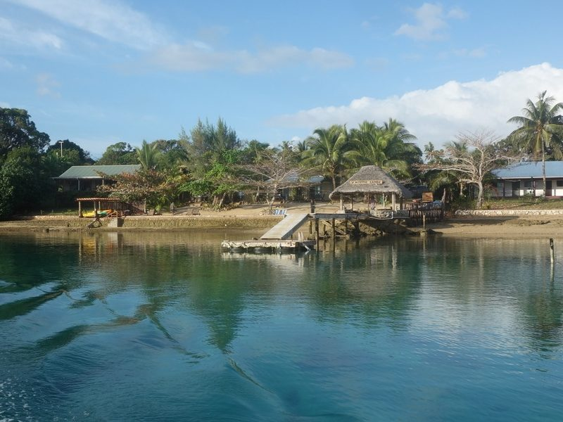 The shore of Neiafu, the second largest town in Tonga. Small jetty and blue water with a pristine beach.