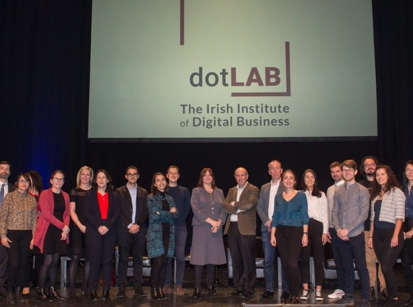 DOTlab researchers standing together in a line in front of the new logo for the research centre.