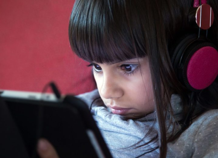 A little girl wearing pink headphones, playing a game on a tablet device.