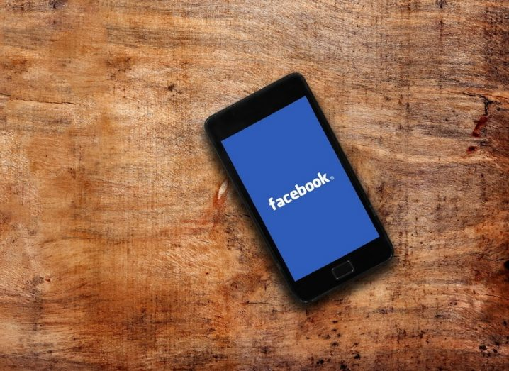 Facebook logo on display of a smartphone, resting on a wooden surface.