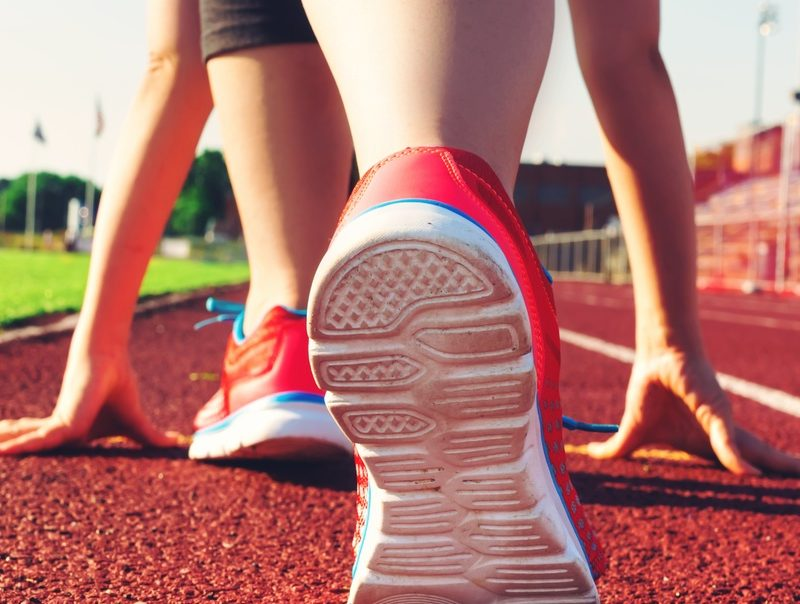 View of an athlete's running shoes and hands on a red track, preparing to race.
