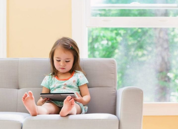 A little girl sitting on a grey sofa in a bright room, watching a film on a tablet device.