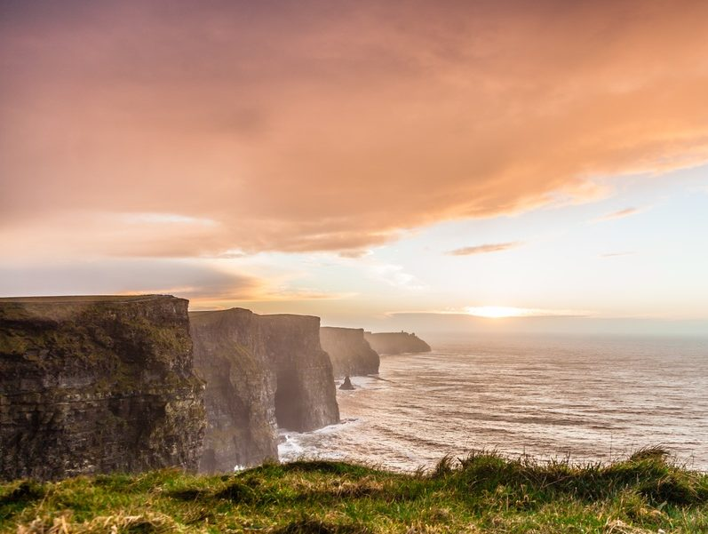 Cliffs of Moher at sunset in Co Clare, with pink clouds in the sky.