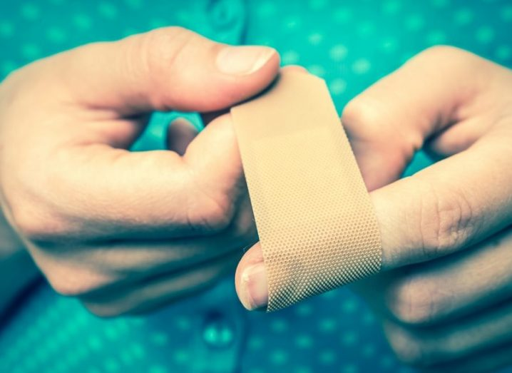A close-up image of a woman applying a plaster bandage to her finger.