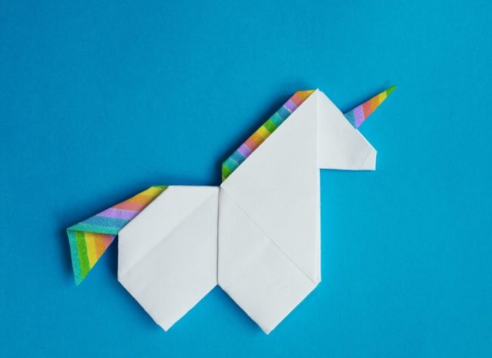 Handmade white paper origami unicorn with rainbow hair on blue background.