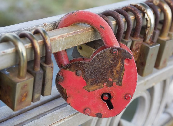 Red heart-shaped lock hanging on a bridge with small brass locks either side of it.