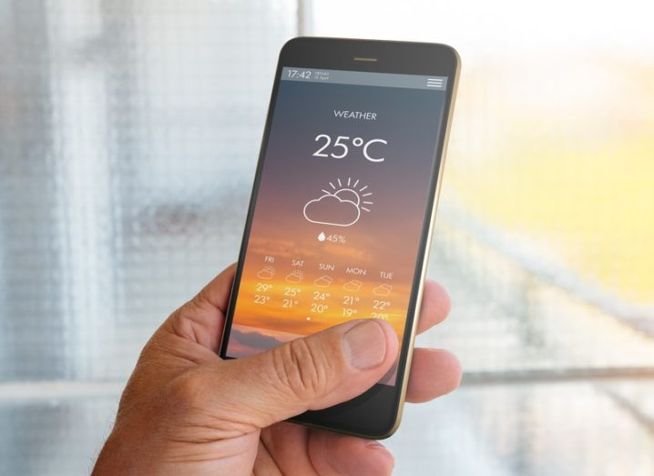 A hand holding an iPhone displaying a weather app showing the temperature and cloud cover for the day.