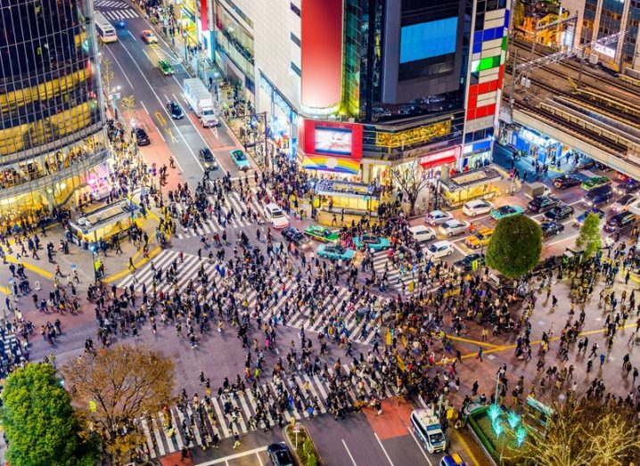 Aerial view of Shibuya crosswalk in Tokyo, Japan with hundreds of pedestrians walking among skyscrapers.