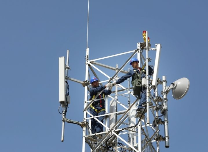 Huawei engineers working on a mobile network mast. Blue sky in background.