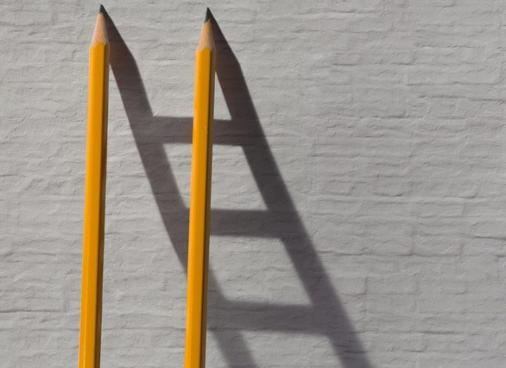 Two pencils and a shadow in form of ladder near the stone wall. Collaboration concept.