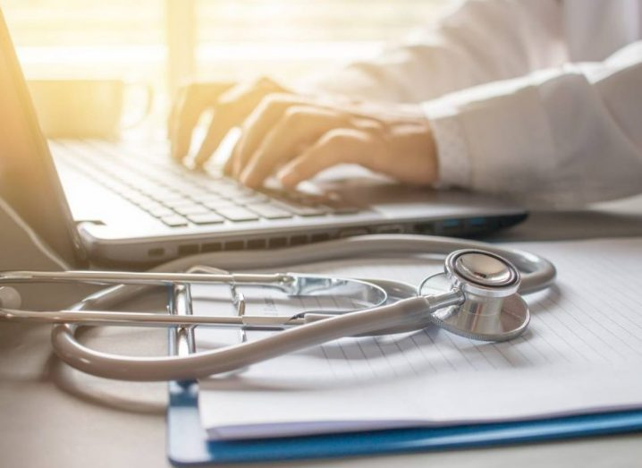 A doctor typing on a laptop with a stethoscope on the desk in the foreground.