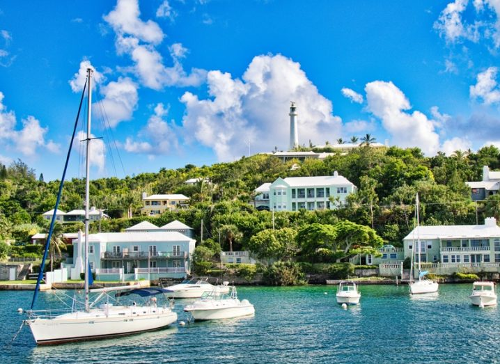 The coast of Bermuda, a tropical island with lush greenery and villas, with yachts floating in the ocean.