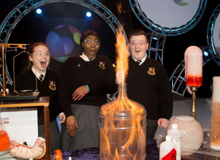 two female and one male students in school uniforms gasp in awe at a science experiment set aflame.