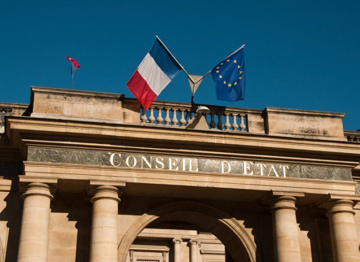 Council of State building in Paris with French and EU flags under a blue sky.