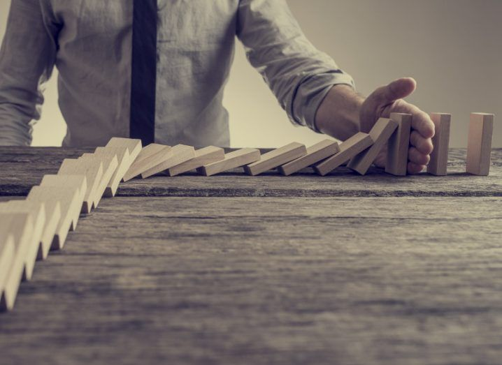 Businessman preventing dominoes from crumbling with palm on an old wooden table.