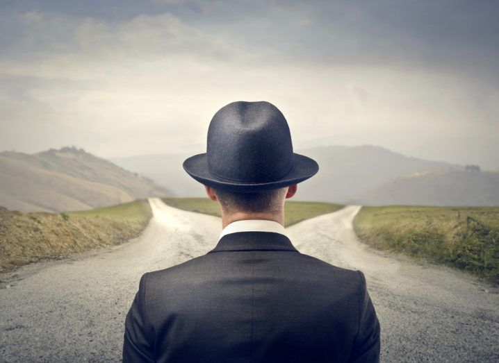 Man in hat stands at a fork in the road.