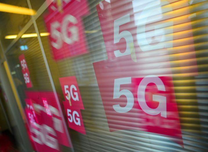 Images of 5G cards on a window in Deutsche Telekom pink branding.