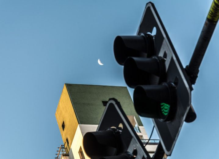 Traffic lights, building and the moon.