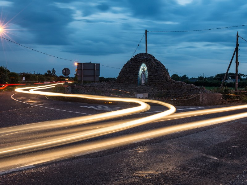 Traffic lights swirl around a religious statue on outskirts of an Irish town.