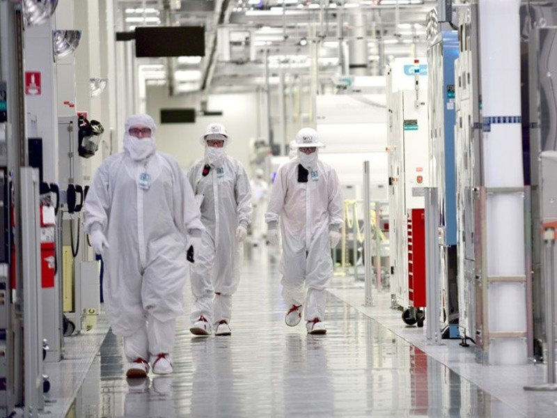 Intel workers in white clean room suits at a wafer fabrication facility.