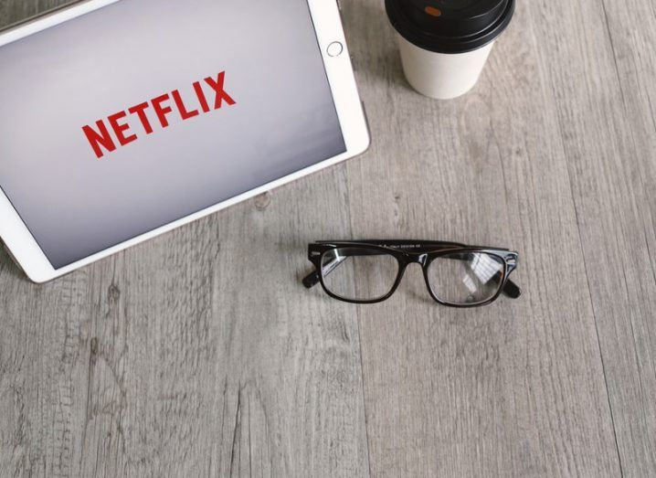 Netflix app icon on an iPad tablet screen with eyeglasses and takeaway coffee cup.