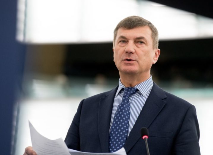 Andrus Ansip wearing a navy suit, holding documents as he addresses a crowd.