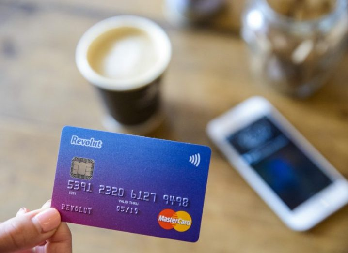 A hand holding a blue and pink Revolut payment card with a cup of coffee and phone on a table in the background.