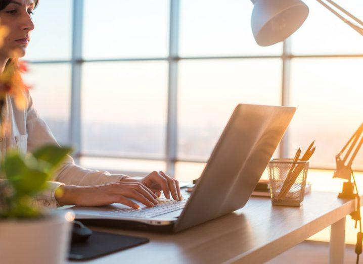 Woman with long hair working from home on a laptop with sun shining through window.