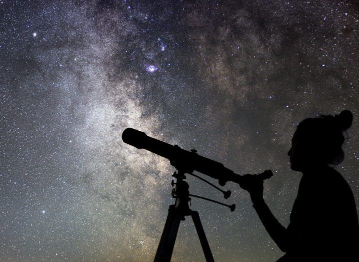Shadow of a woman using a telescope to gaze into a glittering night sky background.