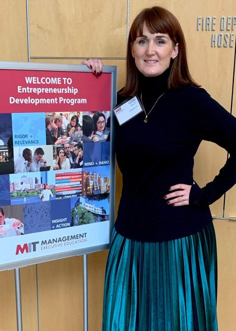red-haired woman with black polo neck and teal pleated skirt standing beside a welcome sign at MIT.