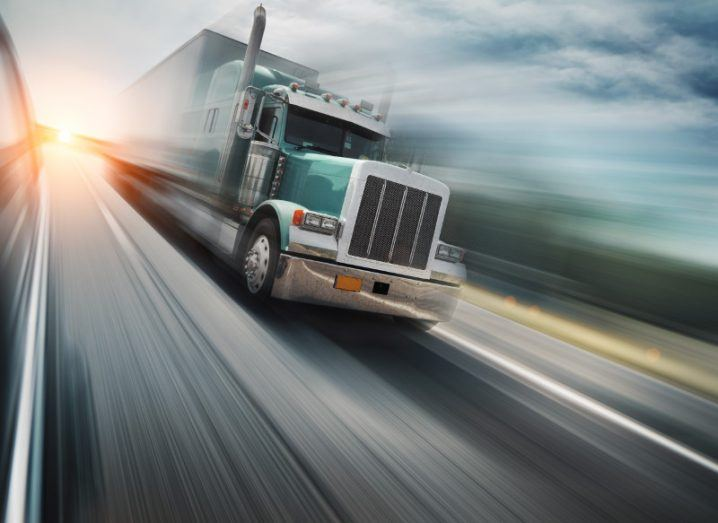 motion image of aqua green shipping truck with motorway blurred in background.