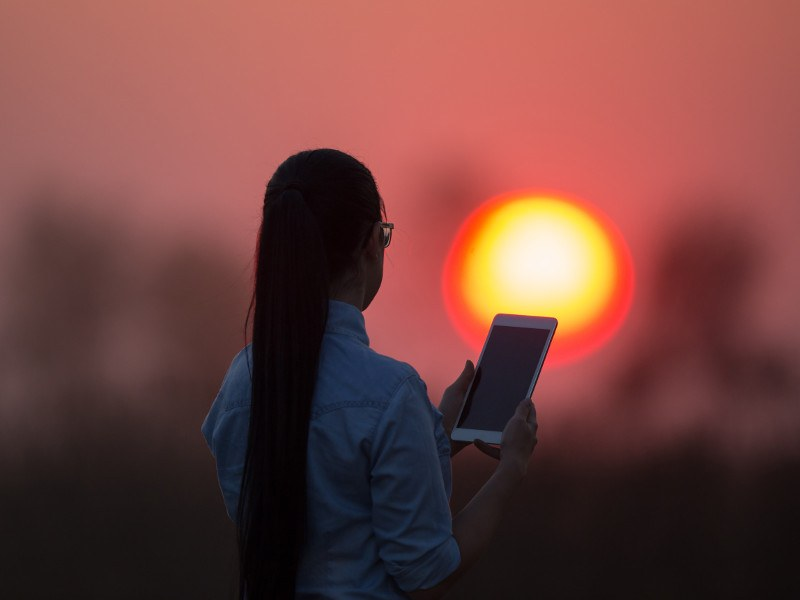 Woman holding a tablet computer in a field at sunset.