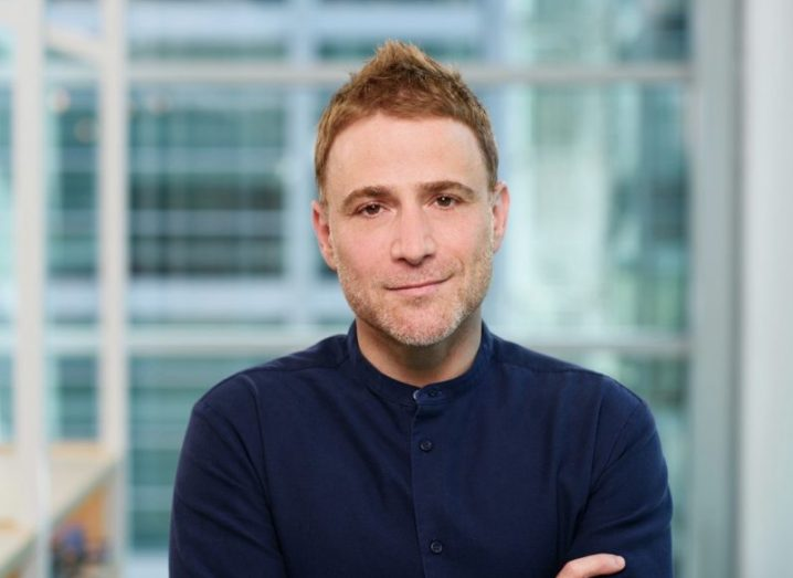 Stewart Butterfield, wearing a navy button-up shirt, smiling with a glass panel in the background.
