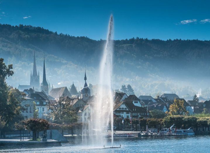 Old city of Zug, Canton Zug, Switzerland, with a water fountain shooting from lake to sky.