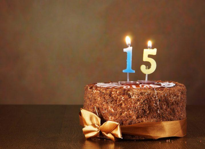 Birthday chocolate cake with burning candles as a number fifteen on brown background.