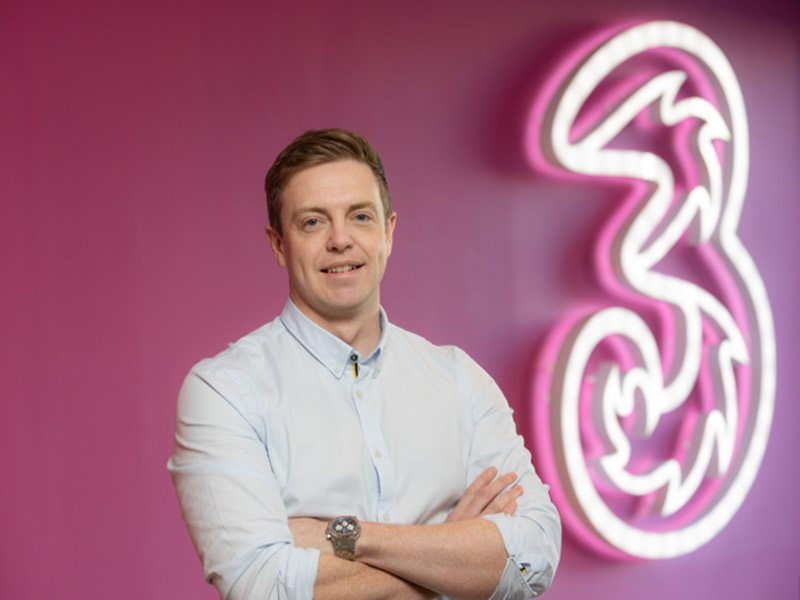 Man in white shirt stands with arms folded against a pink wall with a giant neon sign denoting Three Ireland logo.