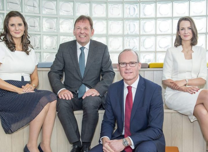 From left: Rebecca Kelly, Michael Kelly and Clare Kelly from Glandore with An Tánaiste Simon Coveney, sitting on modern bench in airy co-working space.