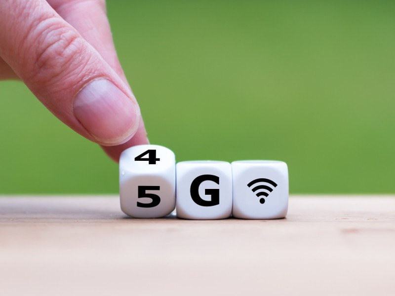 Picture of a hand turning dice with 4G and 5G wireless symbols against a green background.