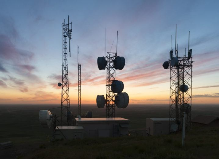 Silhouettes of radio towers on a hill against a setting sun.