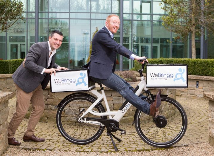 Two men larking about on a bike with the WeBringg logo outside a glass building.