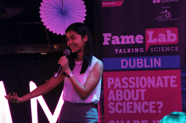 A young woman holds a microphone and gestures while speaking on-stage at FameLab in Dublin.
