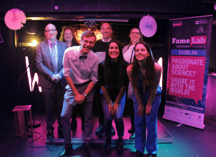 Two rows of people pose for a group photo on the FameLab stage. The three people in front are crouching slightly.