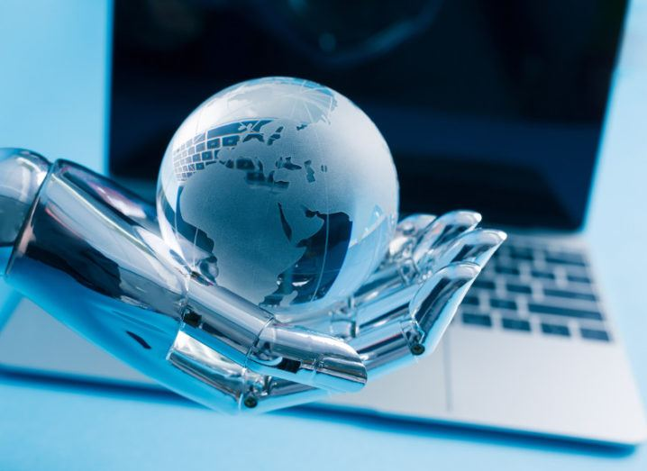 A robot hand holds a globe in front of a computer against a blue background.