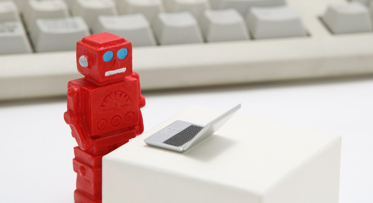 A small red toy robot on a tiny toy laptop, looking up AI influencers. There's a full-size keyboard in the background.