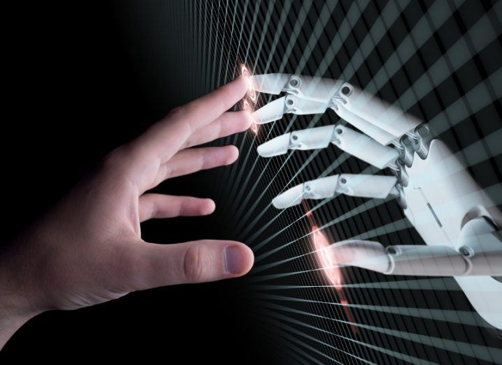 A human hand touches a robot hand, separated by streams of data.