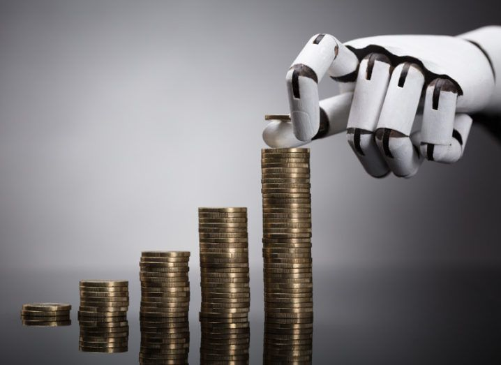 Picture of a white robot hand counting euro coins against a grey background.