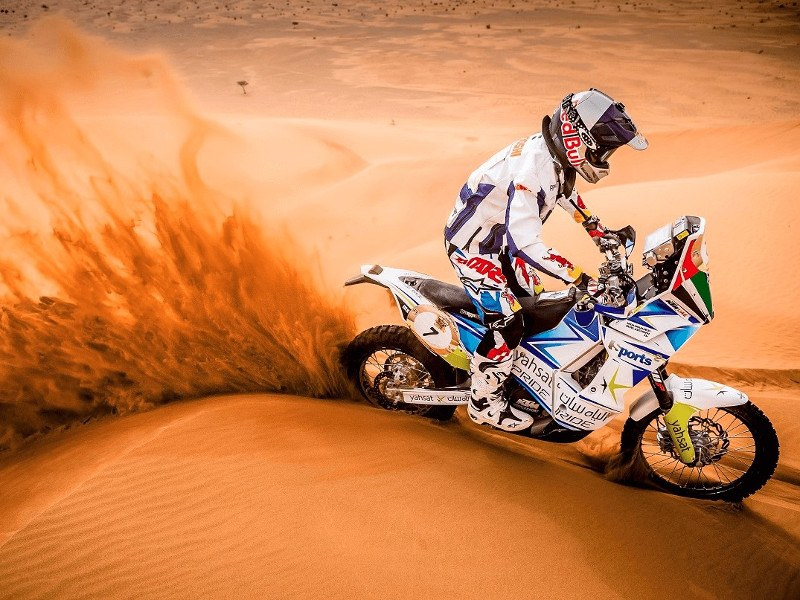 A picture of a motorcyclist driving through the desert, kicking up orange sand in his wake.