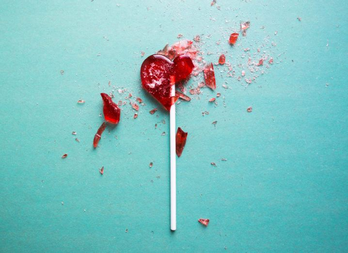 A shattered heart-shaped red lollipop against a turquoise background.