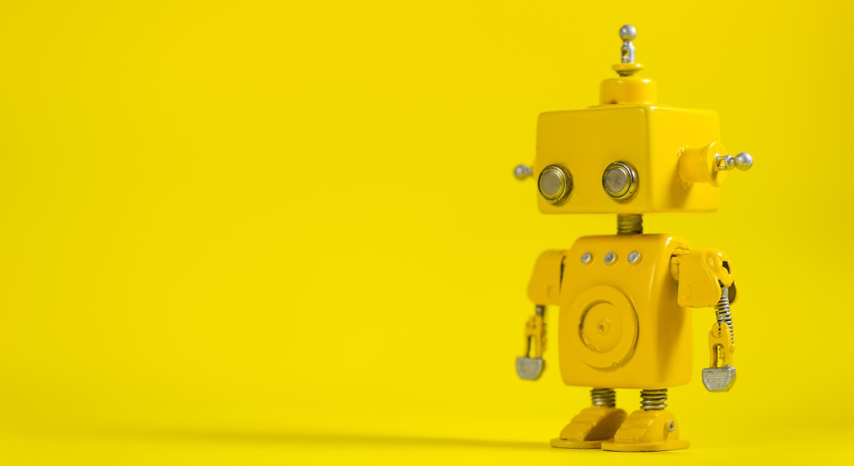 A little yellow toy robot looking askance against a bright yellow background.